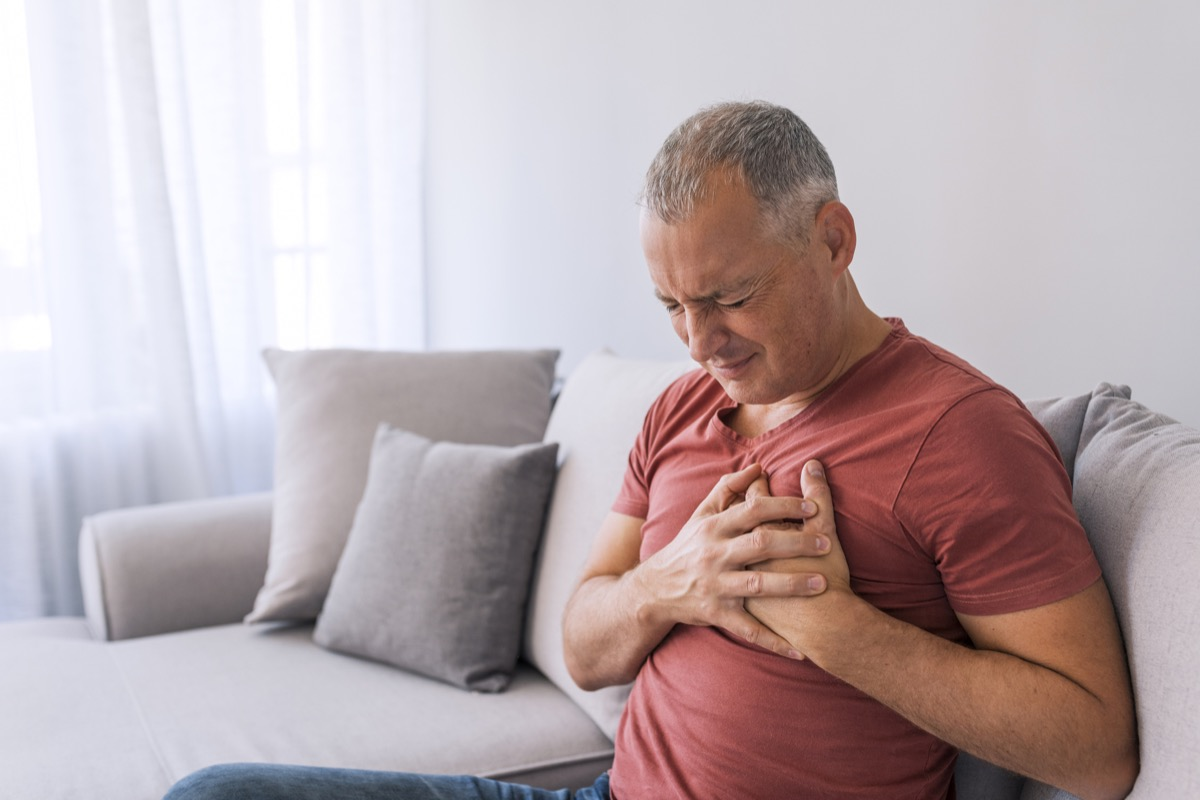Man holding chest from heartburn