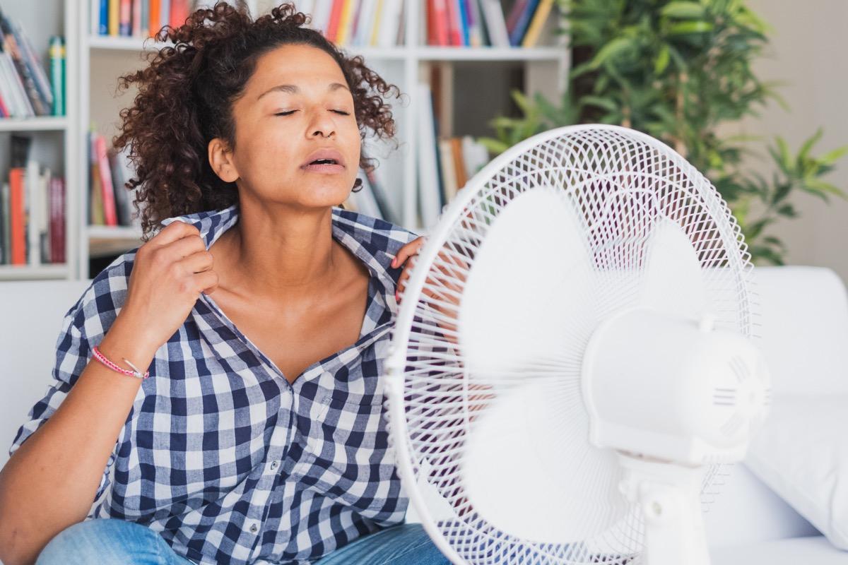 Woman using fan because she has heat intolerance