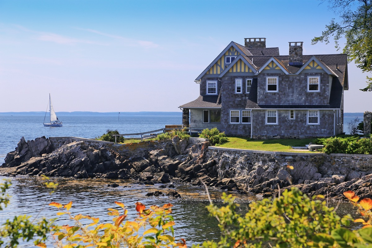 Luxury Waterfront House with grey shingle exterior, Kennebunkport, Maine, New England, USA. Rocky shore, ocean waters, sailboat, green and yellow bushes, trees, and blue sky with clouds are in the image.
