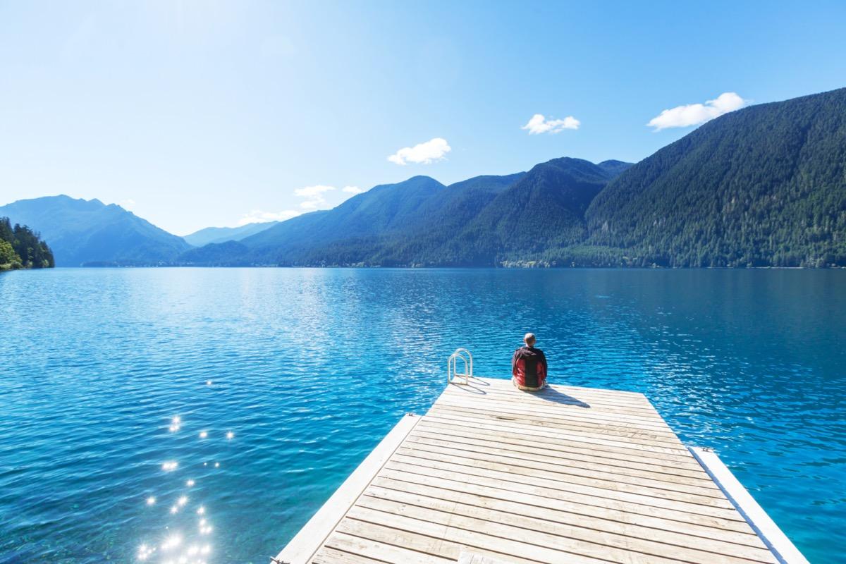person sitting on a dock at lake crescent washington