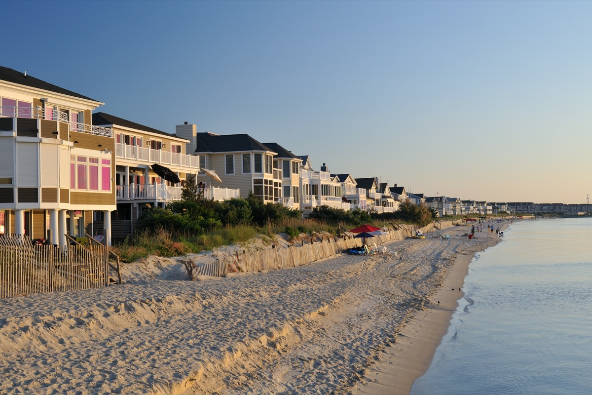 Pristine beach and luxury villa houses with people enjoying beach activities in the background on the Cape Henlopen of Delaware, where thousands of visitors come to enjoy ocean swimming and sunbathing during summertime.