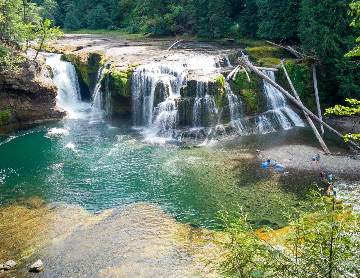 people swimming in turquoise waterfall