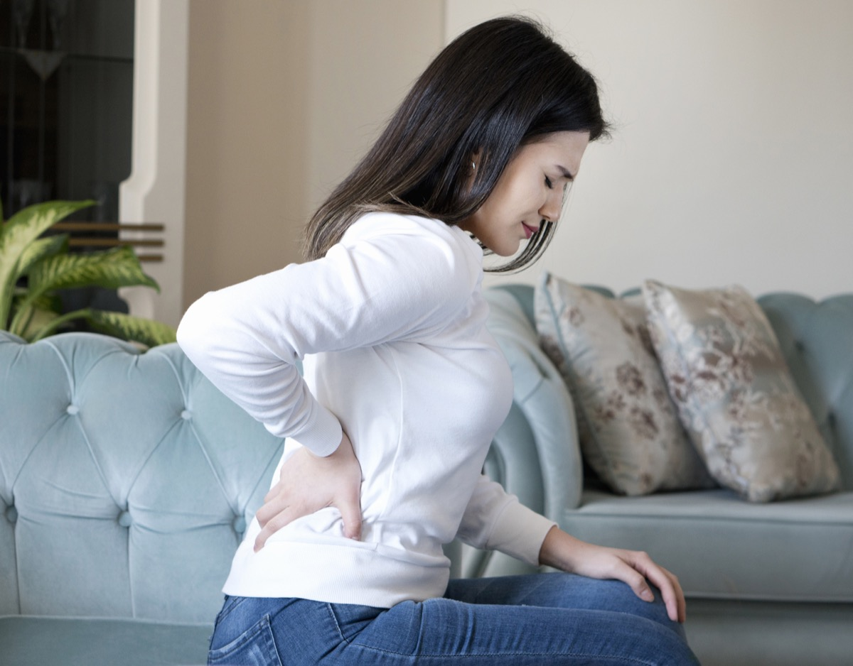 Woman with back pain holding back sitting on couch