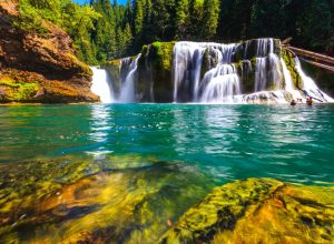 turquoise swimming hole with a waterfall