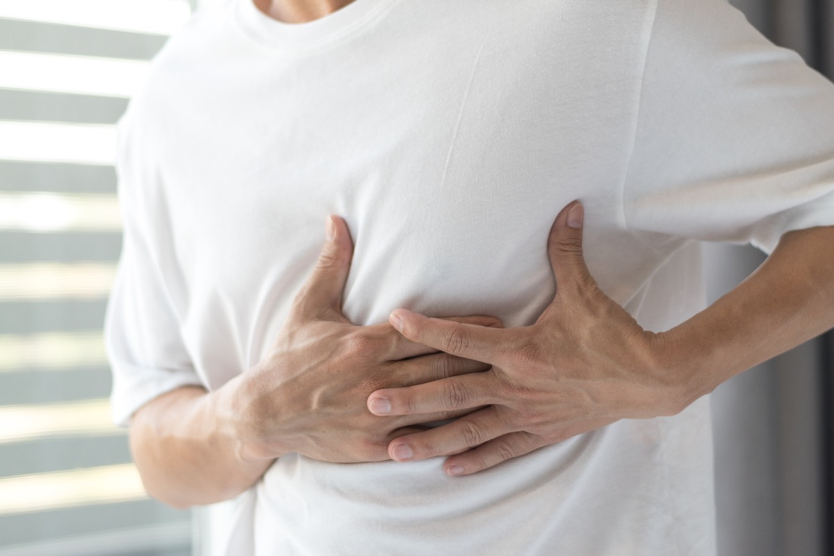 Man with hand on lungs because of discomfort