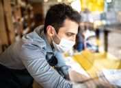 Young small business man owner with face mask working on checkout