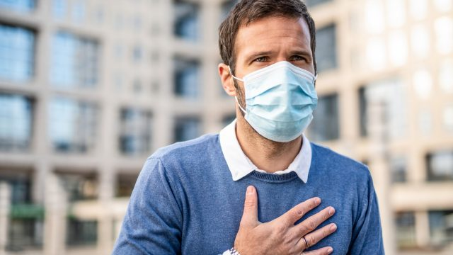 Mid adult man having health issues. Holding his chest and wearing a protection mask.
