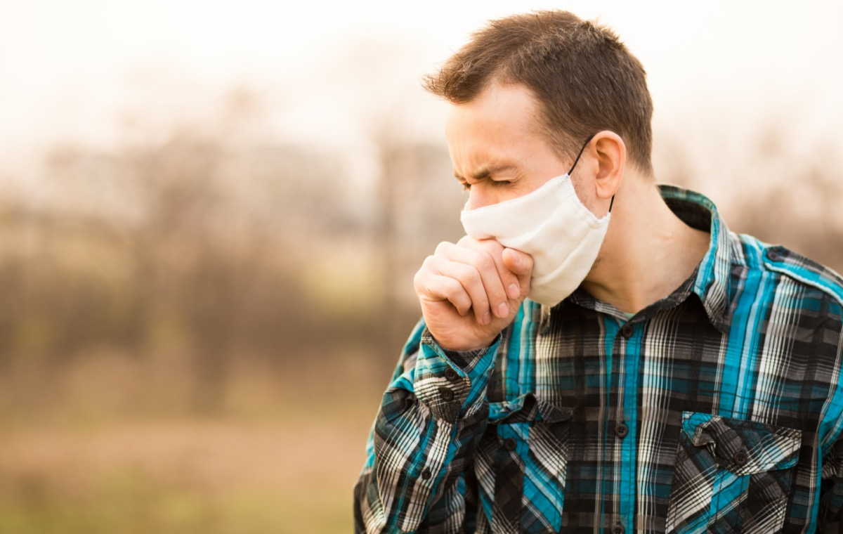 young man standing outdoors wearing face mask and coughing