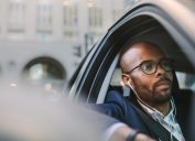 Relaxed businessman wearing earphones and listening musing while driving a car. African businessman traveling in a car through city street.