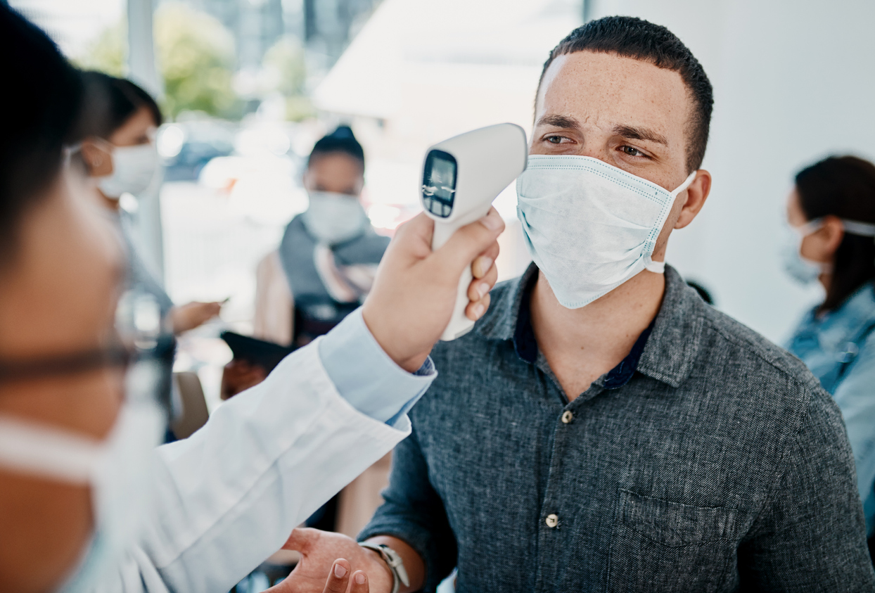 A young man wearing a face mask getting his temperature taken with an infrared thermometer by a healthcare worker during an outbreak to check for coronavirus