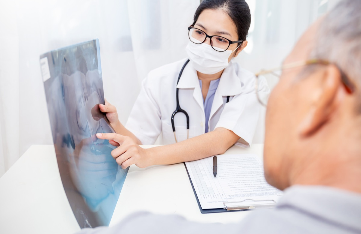 Portrait of woman doctor wear protection face mask show patient some information on digital tablet clip board, patient listen to specialist doctor in clinic office. Epidemic flu or Coronavirus.