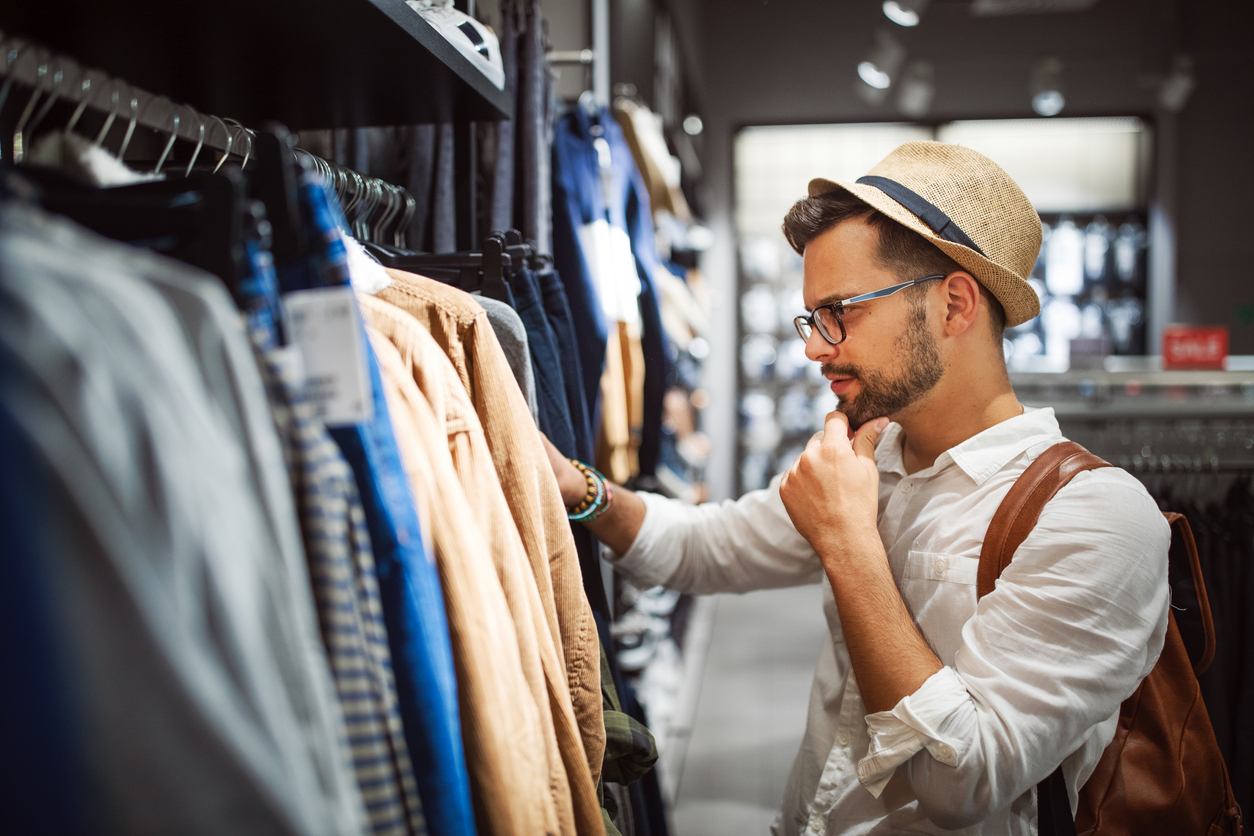 A young man in a hat and glasses shops for clothes in a store