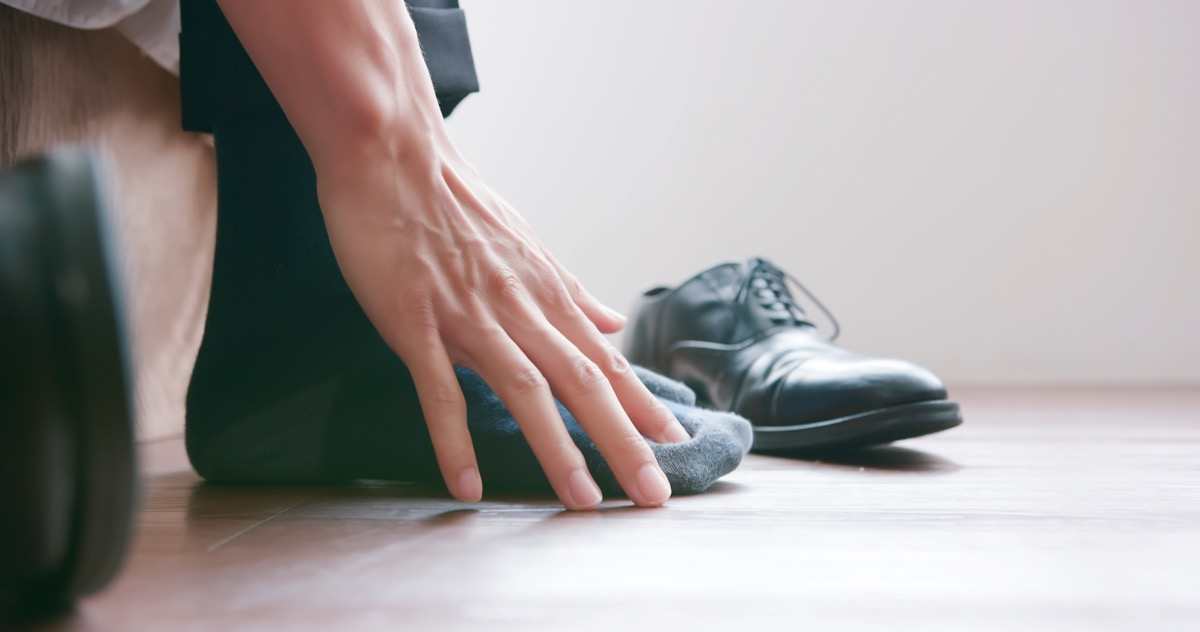 business man scratch the itch by hand with athlete foot problem