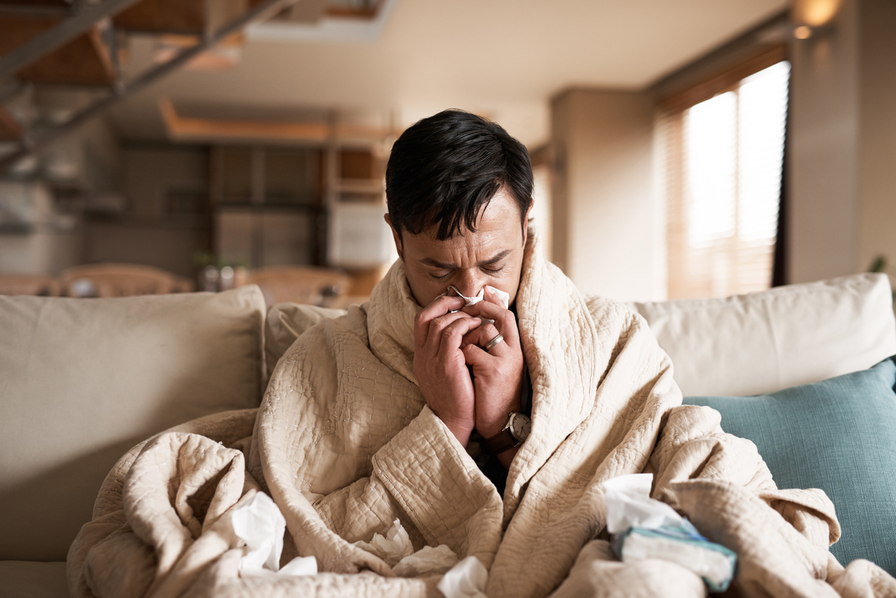 A man wrapped in a blanket sits on the couch blowing his nose with flu symptoms, as flu season overlaps with the coronavirus pandemic