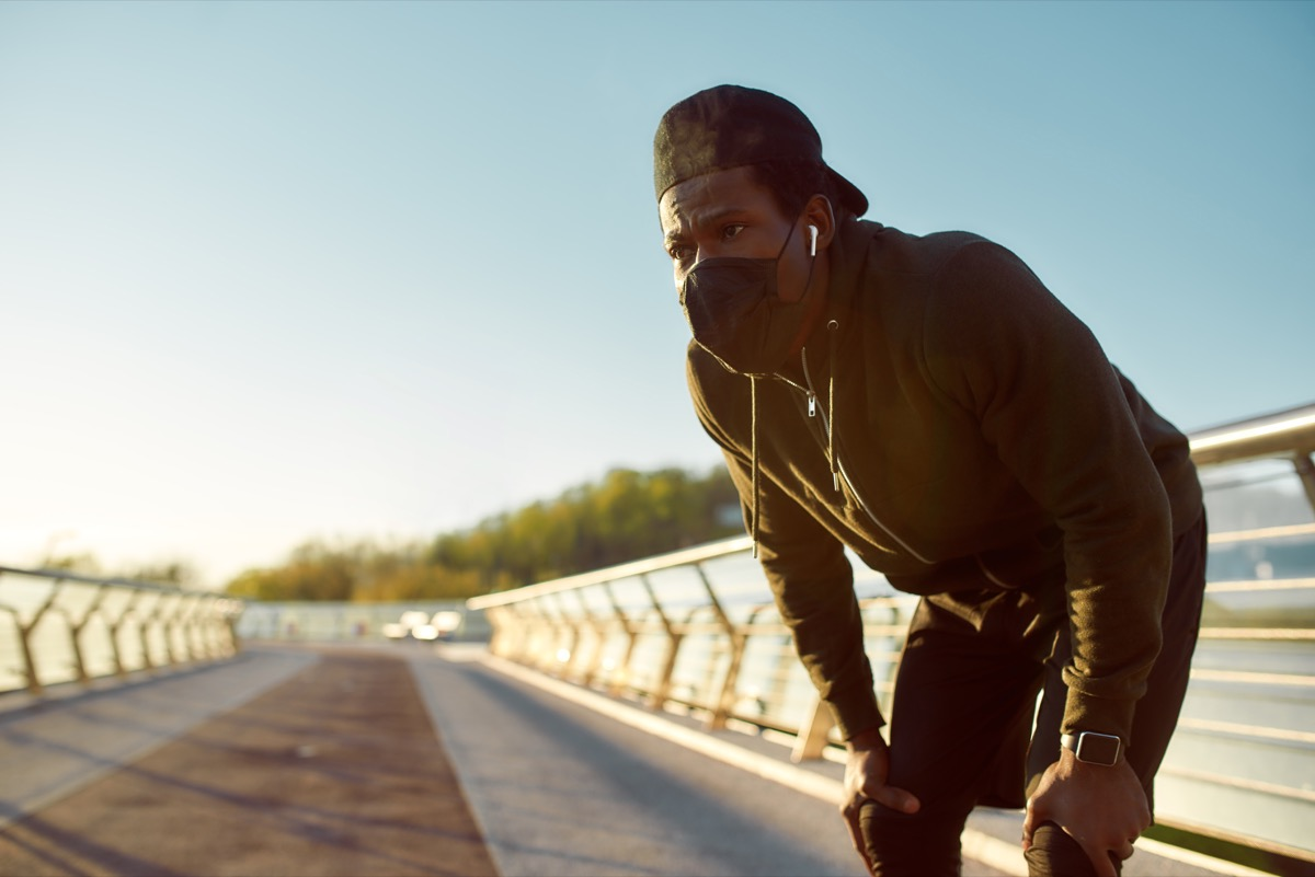 tired jogger in protective mask resting after running while standing on the bridge in the morning. Running at sunrise. Sport during quarantine. Covid-19. Protection. Staying active