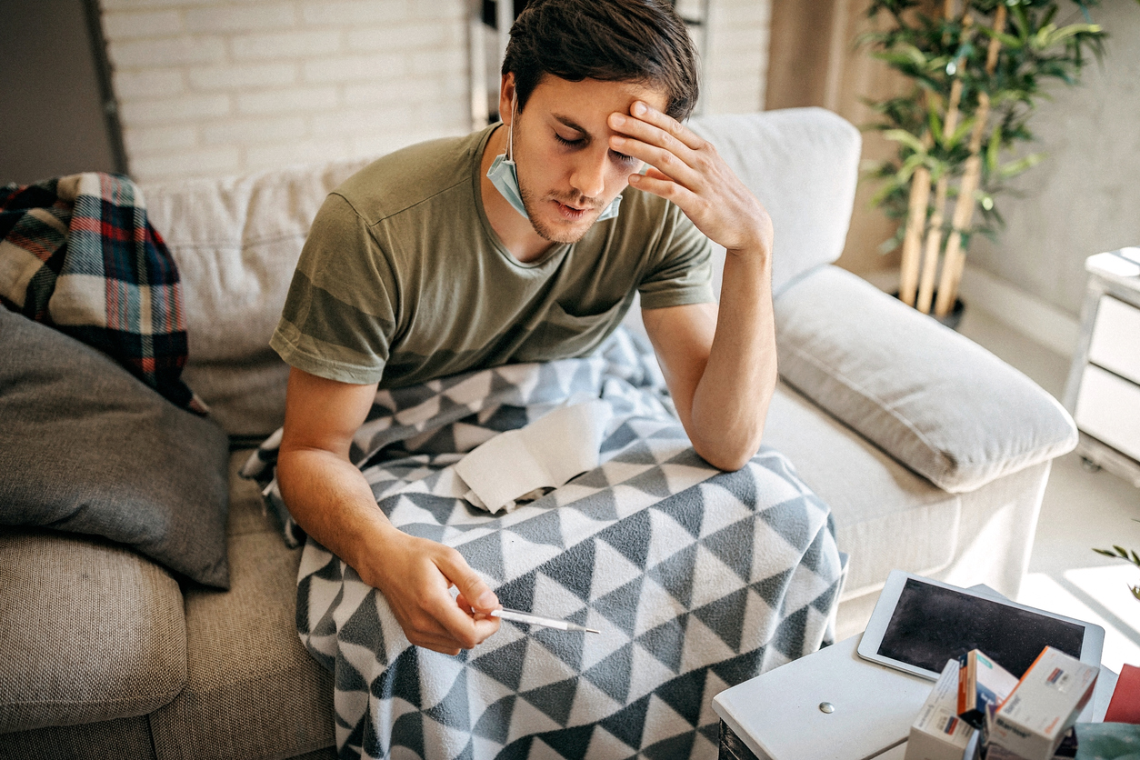 A young man with coronavirus symptoms sitting on the couch reading a thermometer with a face mask pulled down under his chin