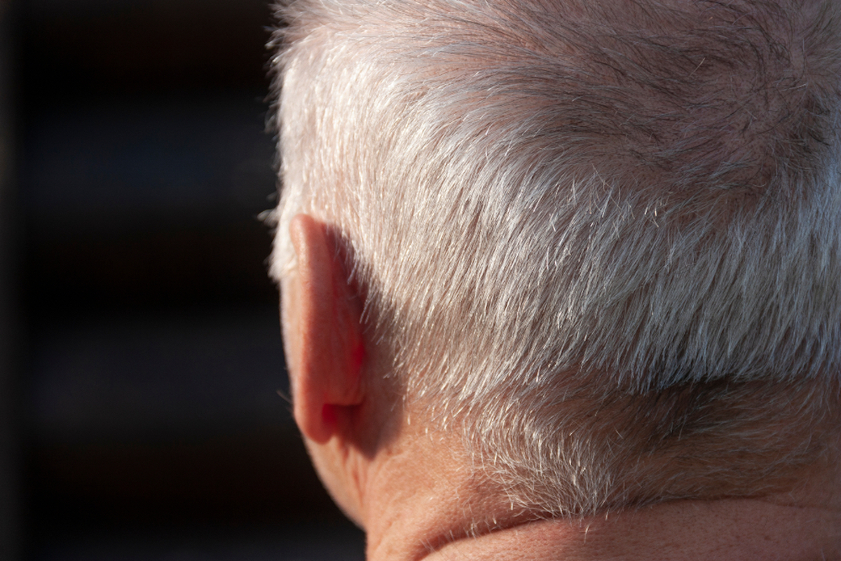 old man photographed from behind, focus is on ear