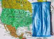 A map of the United States with a face mask laid over it to show the spread of COVID