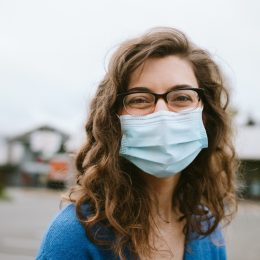 A young woman smiles while wearing a protective medical mask outdoors. Happy still in the face of the global pandemic of Covid-19.
