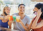young people drinking with masks on chin