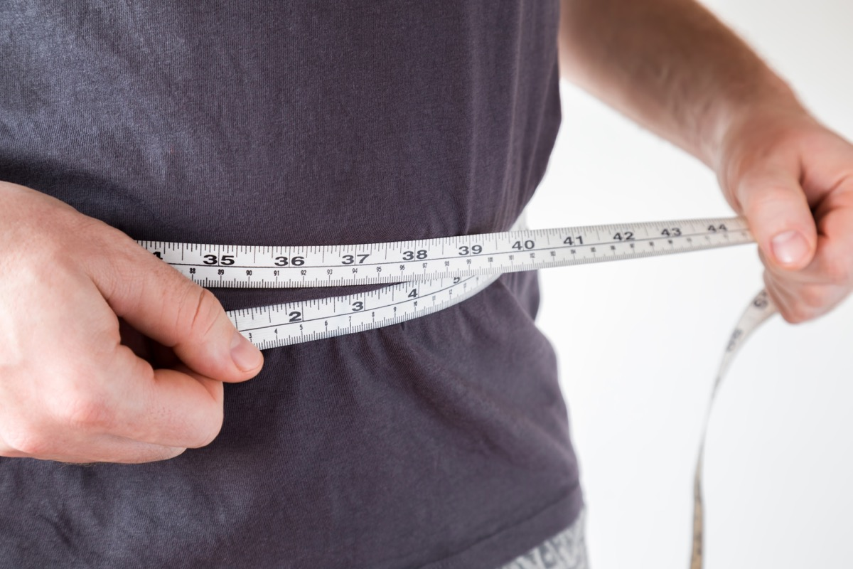 Slim man measuring his waist. Healthy lifestyle, body slimming, weight loss concept. Cares about body.