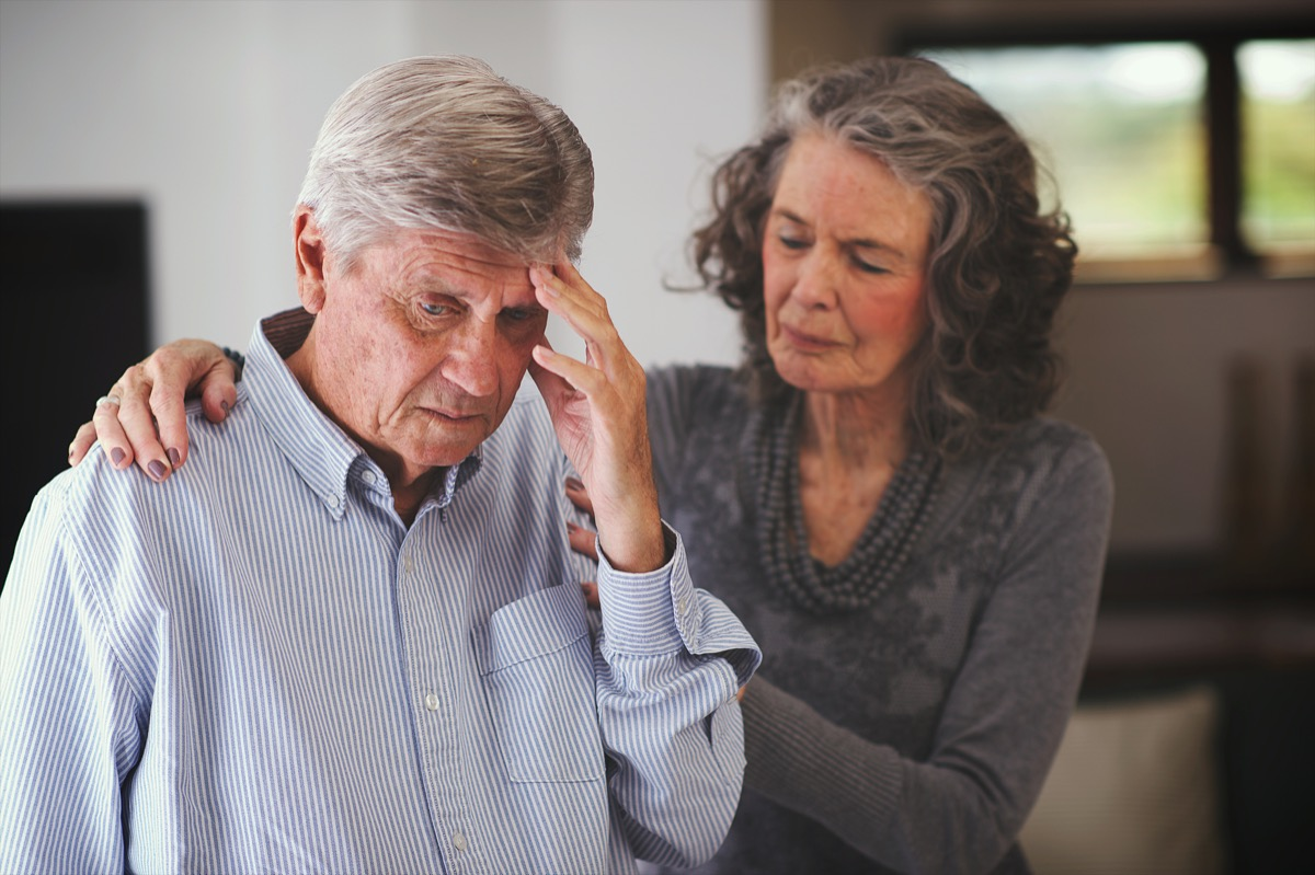 Woman helping man with memory problem at home