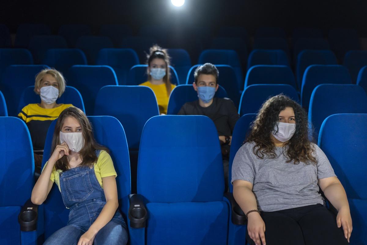 Group of people watching movie after Coronavirus pandemic. Social distancing