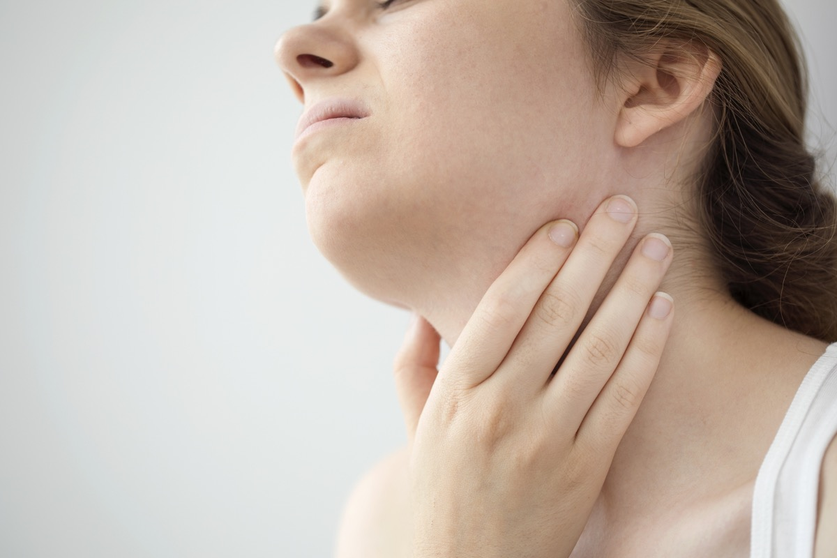 Woman feeling pain in the throat from swollen lymph nodes