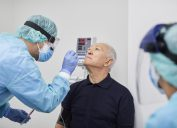 A older man in a blue short has his nose swabbed by a health care worker in full protective gear for a coronavirus test