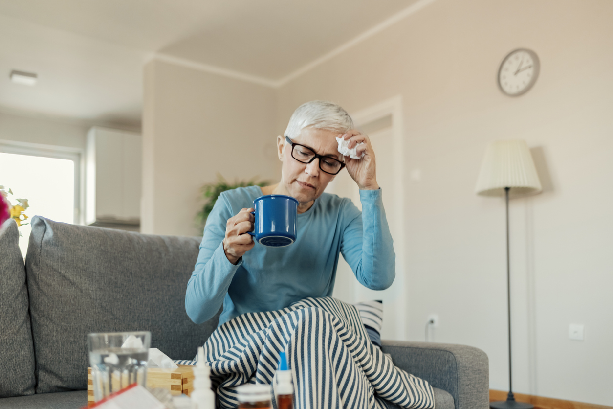 An older woman sits on the couch with symptoms of the common cold, holding a mug and tissue