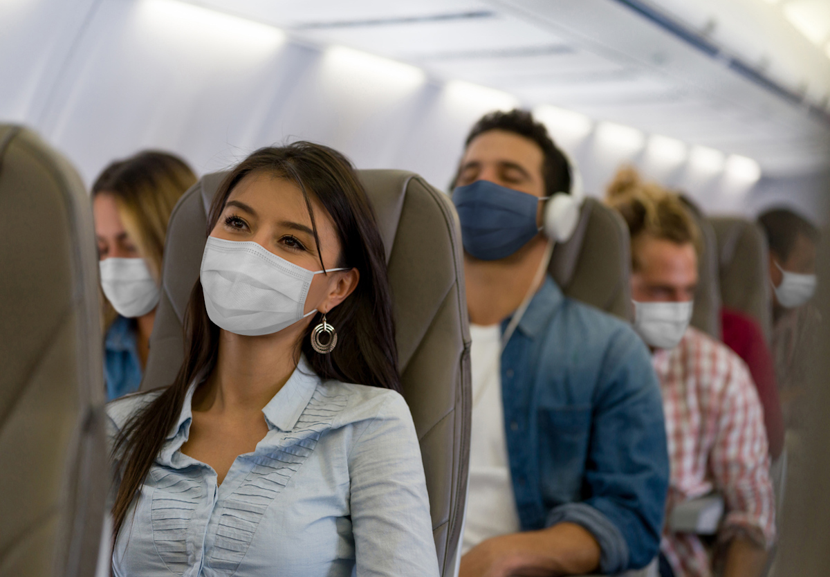Travelers on a plane wearing face masks during the COVID-19 pandemic