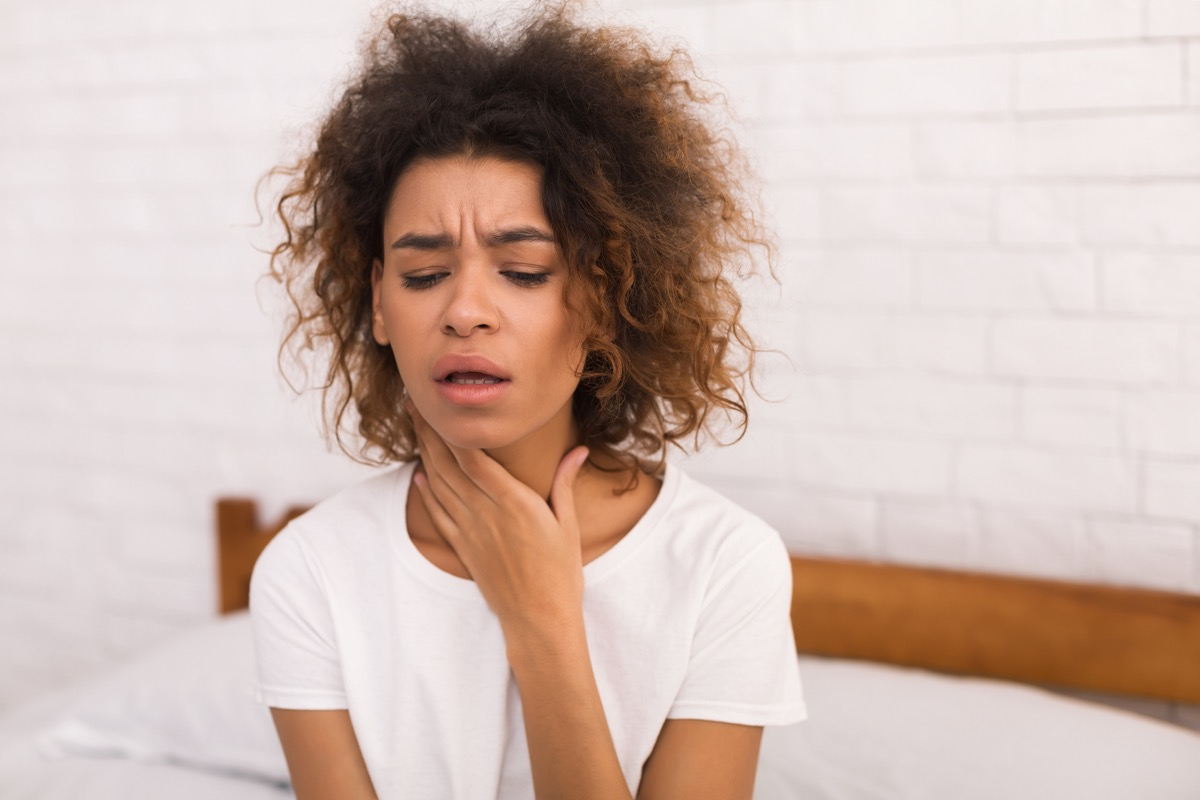 Woman holding her throat because of post nasal drip