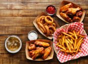 pub appetizers such as chicken wings, onion rings and french fries on a wood table