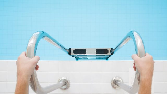 Man's hands holding on metallic ladder. Ready for swimming in the pool. Part of body. Point of view shot. Close up.