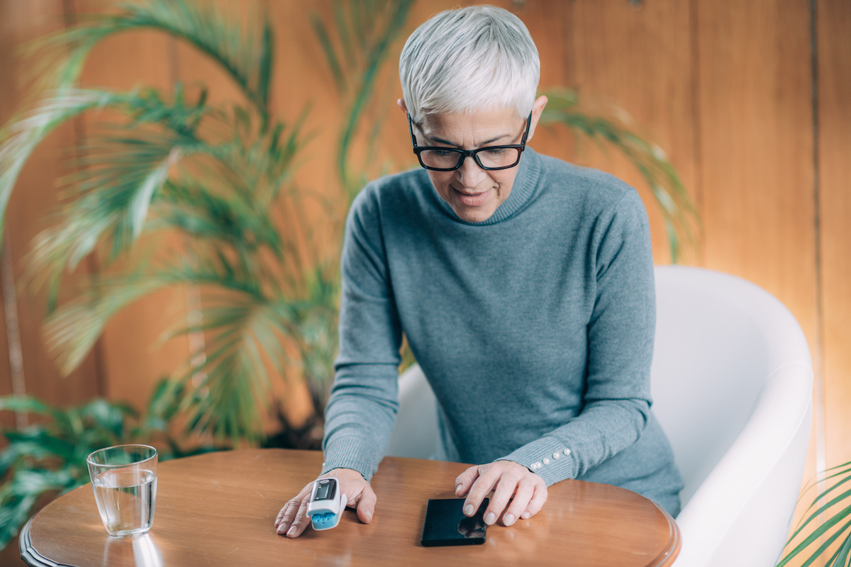 senior woman sitting at a table using a Pulse Oximeter to monitor Blood Oxygen Saturation levels