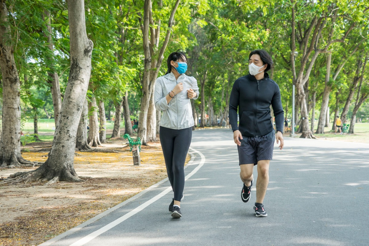 People wearing face masks while running in the park