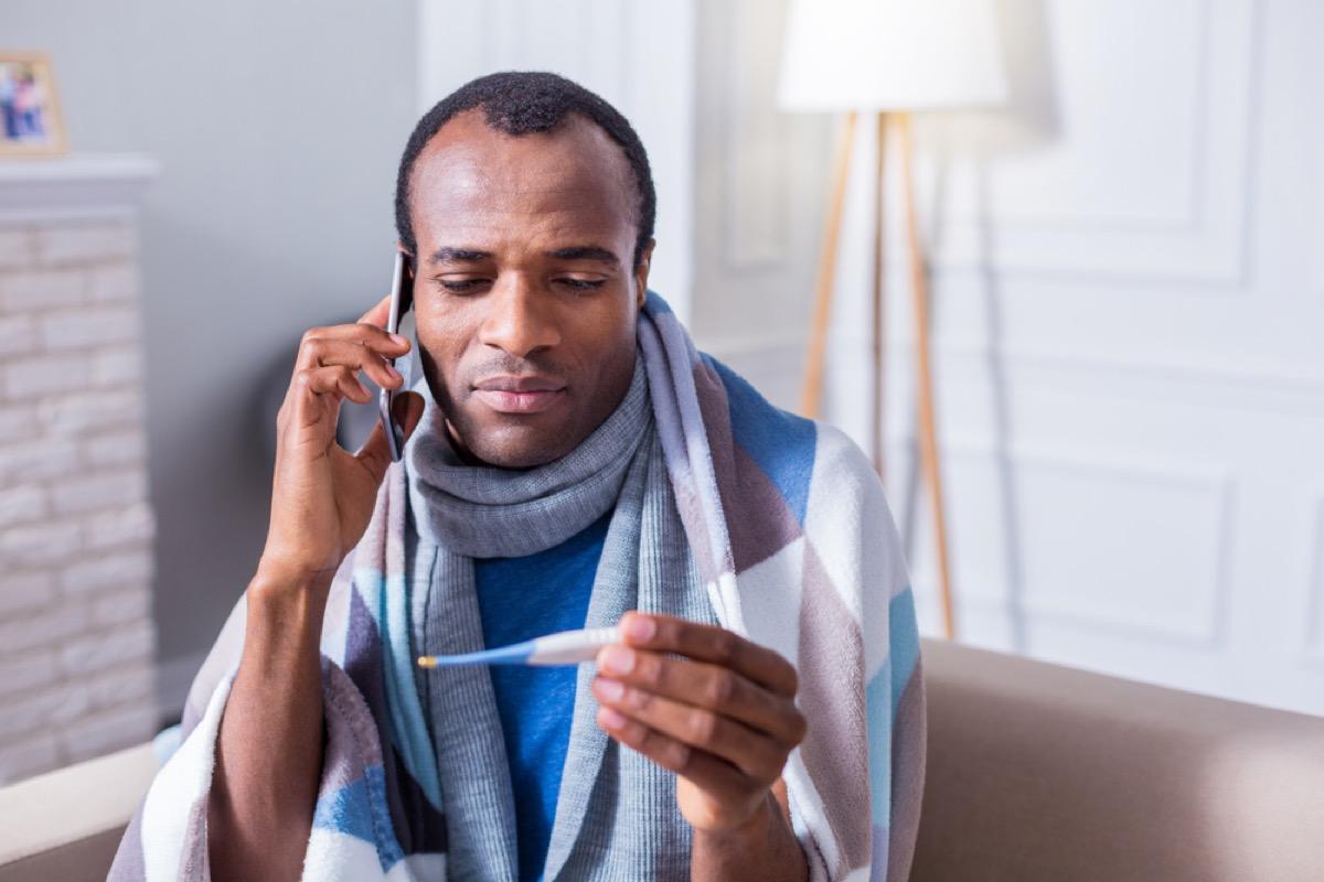 man checking his temperature and making a phone call