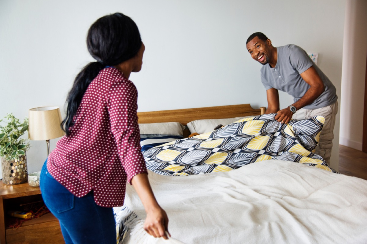 young black man and woman making the bed