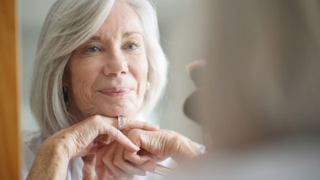 older white woman looking in mirror