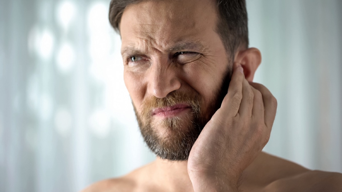 white man pressing his ear and looking concerned