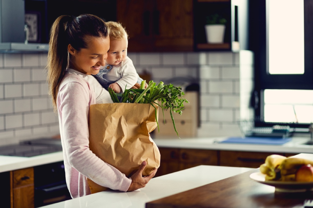 white woman holding baby and a bag of groceries in the kitchen