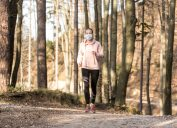 woman jogging with face mask in forest