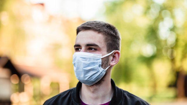 white man wearing a face mask outside