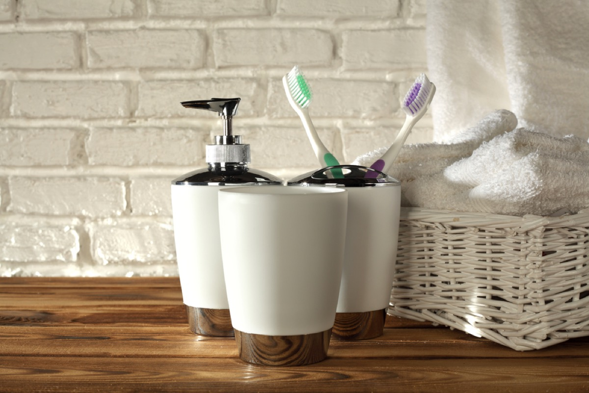 soap dispenser toothbrush holder and towels in bathroom