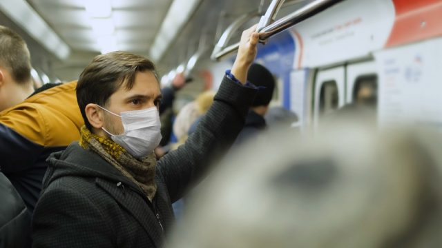 white man with face mask on crowded subway train