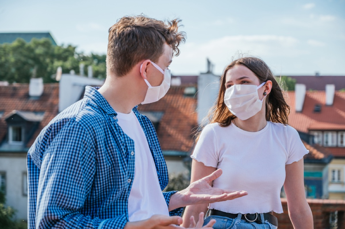 white man and white woman with face masks talking outside