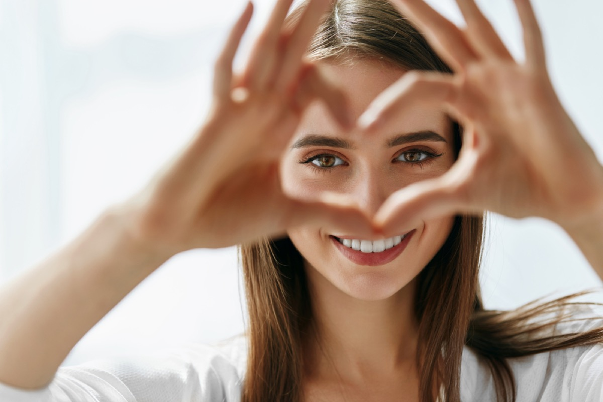 white woman making a heart with her hand around her eyes