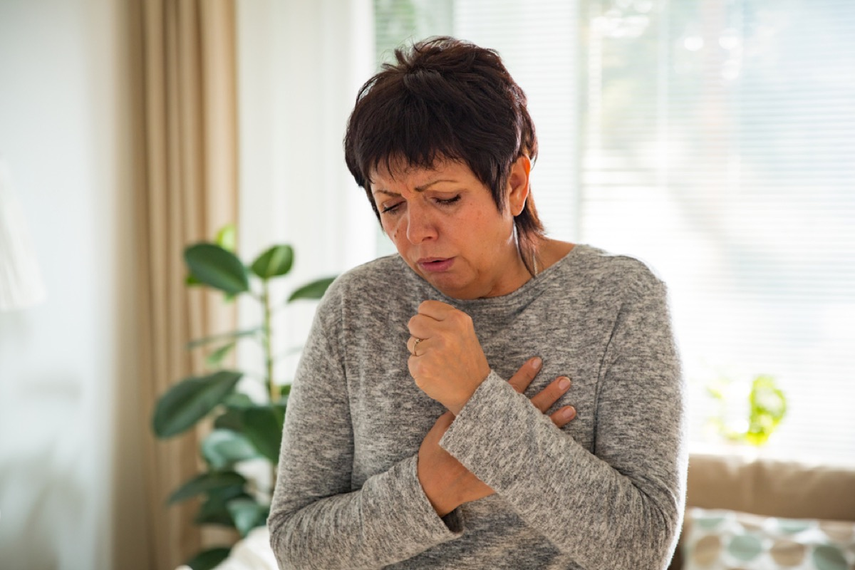 older white woman coughing at home