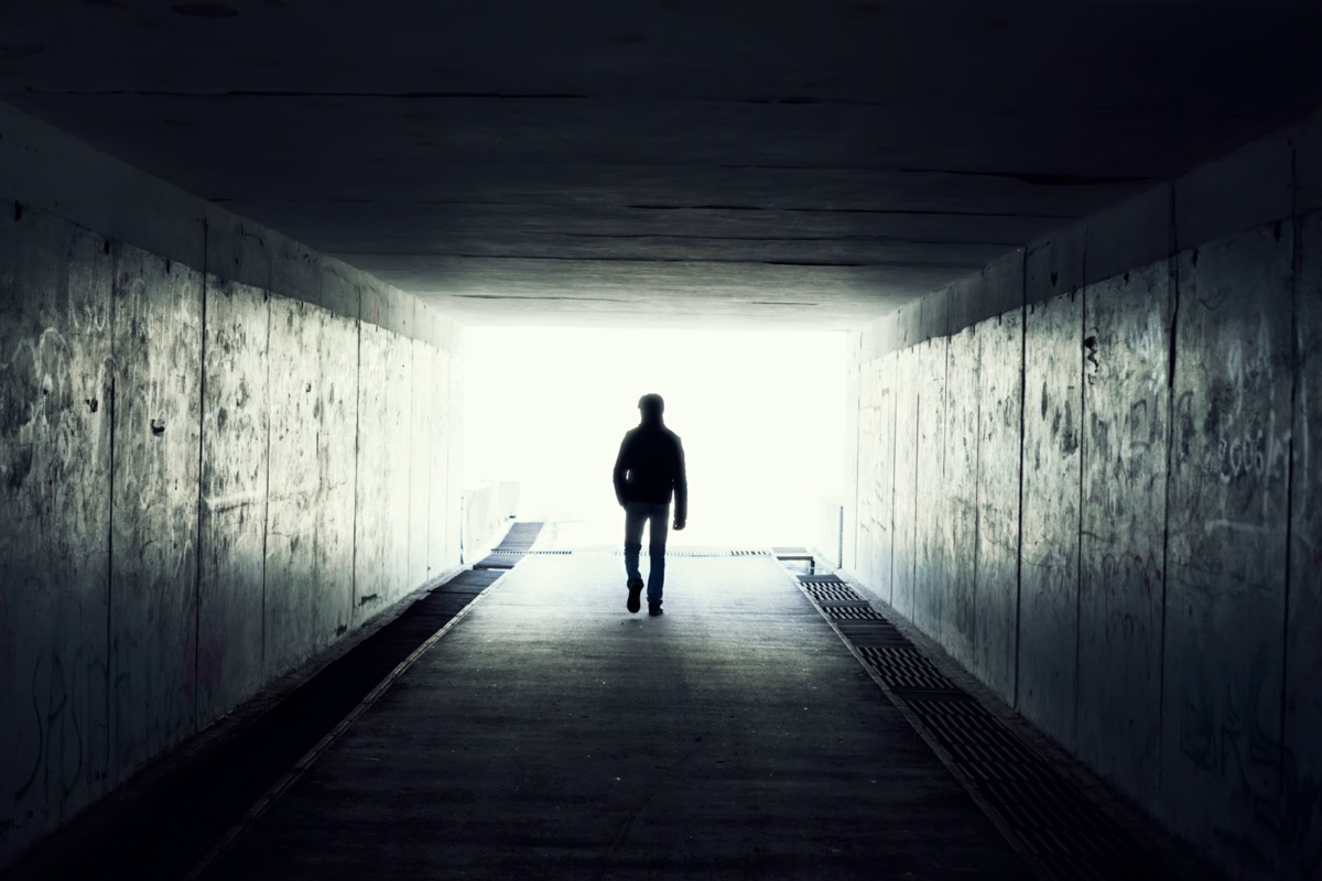 Silhouette of man in a subway tunnel