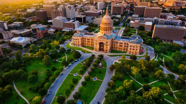 The skyline of Austin, Texas at sunset with the State Capital building in the foreground